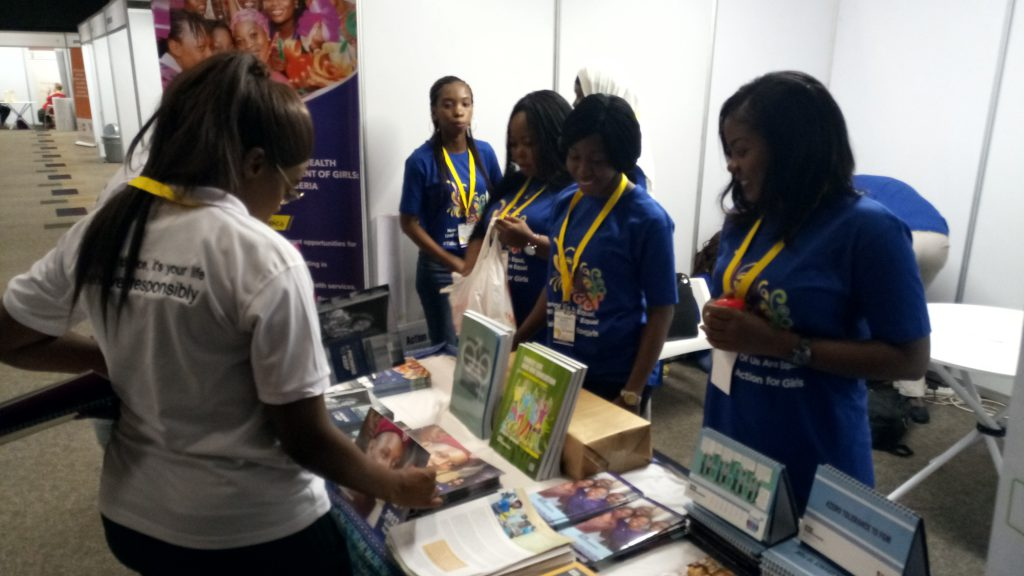 Photo 1: AHI Programme Staff engage with visitors to the AHI booth at ACSHR 2018